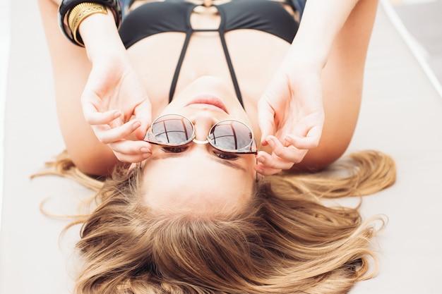 Zomer mode. meisje in de buurt van zwembad. sexy vrouw in trendy zonnebril en modieuze bikini badmode en genieten van luxe vakantie in het resort hotel.