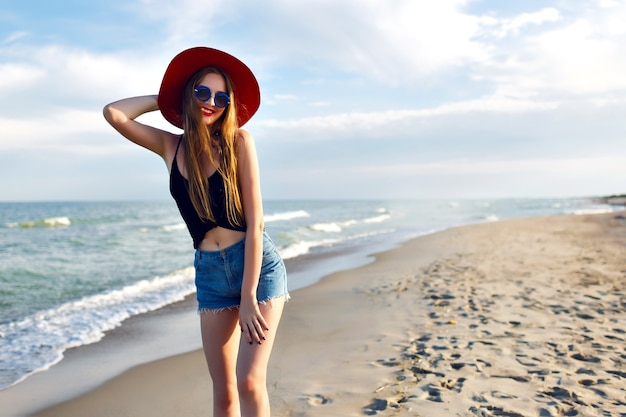 Zomer mode portret van een jonge vrouw die alleen loopt in de buurt van de oceaan, vakantie op het strand, alleen reizen, vintage hoed, zonnebril en denim shorts draagt, slank lichaam, zonsopgang, gezonde levensstijl.