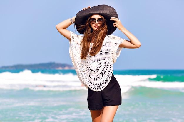 Zomer mode portret van mooie vrouw genieten van winderige zonnige dag in de buurt van de oceaan, vakantie stijl. stijlvol meisje met zwarte kruippakje vintage hoed en grote zonnebril, heldere kleuren