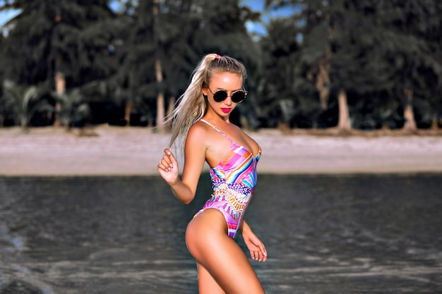 Zomer mode portret van sexy stijlvolle vrouw met perfect gebruinde slanke fit figuur, poseren op tropic strand, ongebruikelijke afgezwakt grijze kleuren van water en planten, kleurrijke bikini en zonnebril, hoogte contrast