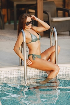 Zomer mode. vrouw in een zwembroek bij zwembad. dame op vakantie.
