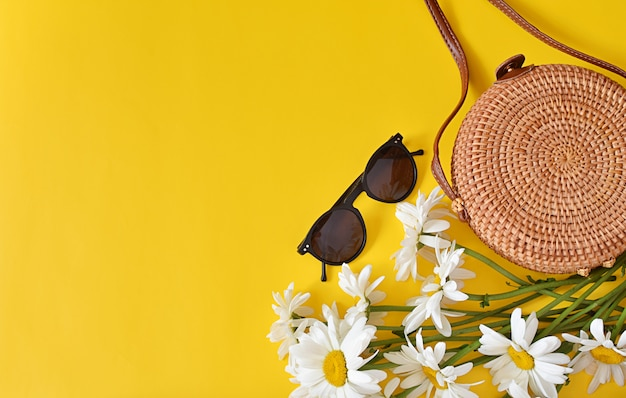 Zomer mode, vrouwelijke accessoires, ronde rotan tas, zonnebril, bloemen op geel.