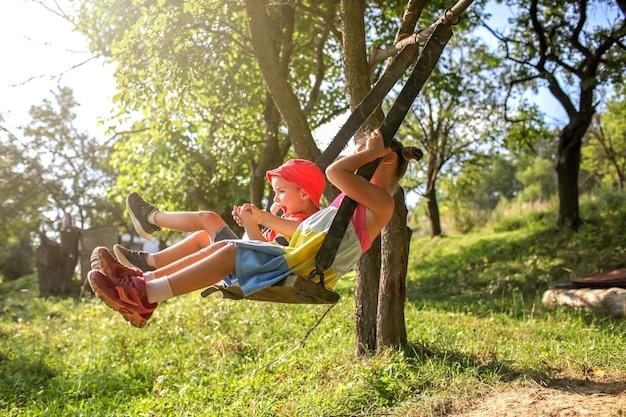 Zomer na lockdown twee kinderen zittend op een schommel in de bergen, ver van de gebruikelijke speeltuin