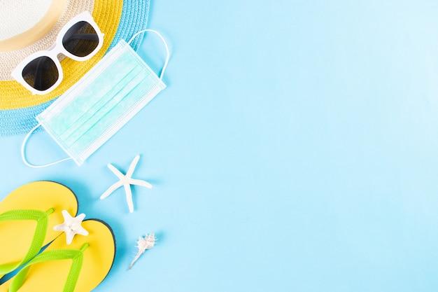 Zomer nieuw normaal concept. strandhoed, zonnebril, medisch masker, slippers op lichtblauwe achtergrond