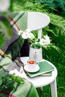 Zomer ontbijt in de tuin kopje thee op boeken bloemen witte wilde roos in vaas theepot warme plaid