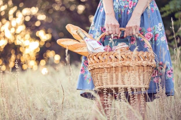 Zomer - picknick in de wei. meisje met een mand voor een picknick met stokbrood, wijn, glazen, druiven en broodjes
