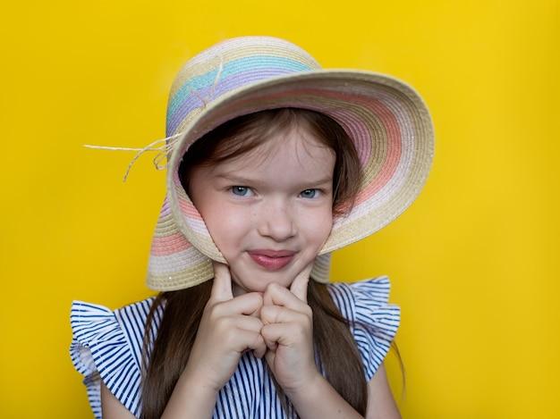 Zomer portret van een mooi klein schattig meisje in een hoed en jurk het concept van een kindermode zomer vakantie kindertijd