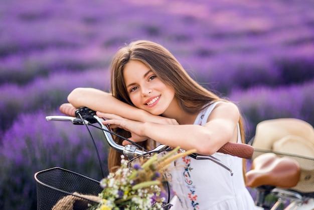Zomer portret van een mooi meisje in lavendel. leuk meisje op een paarse achtergrond.