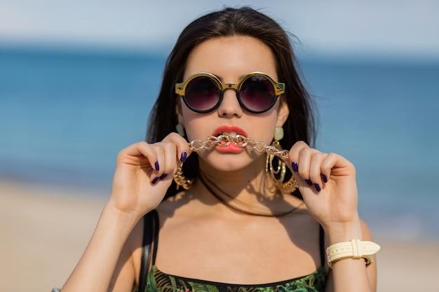 Zomer portret van stijlvolle vrouw met grote trendy accessoires en oorbellen close-up.