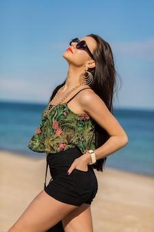 Zomer portret van stijlvolle vrouw met grote trendy accessoires en oorbellen die zich voordeed op het strand.