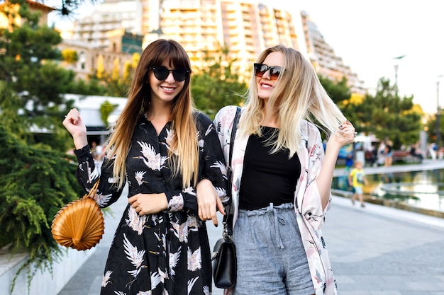 Zomer portret van twee stijlvolle mooie beste vrienden vrouw met geweldige tijd samen, glimlachen en genieten van tijd op straat, elegante trendy kleding smeekt en zonnebril, gelukkige paar, relaties.