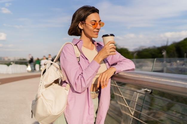 Zomer portret van vrij kortharige vrouw in stijlvolle zonnebril genieten van koffie buiten wandelen in zonnige dag