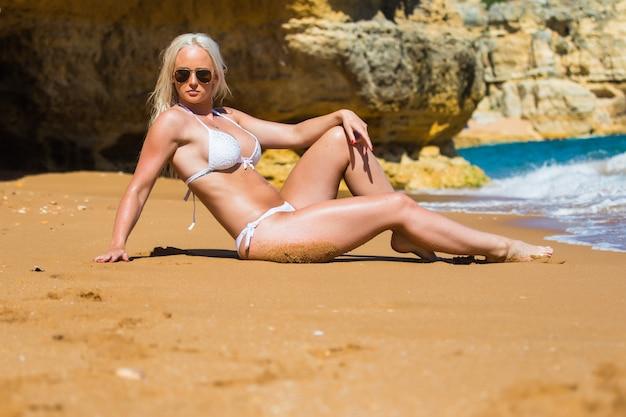 Zomer recreatie en reizen concept. mooie gelooide jonge mode-model in bikini poseren aan de zeekust. vrouw in badmode zwembroek met nat haar en lichaam liggend op een strand