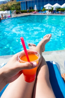 Zomer-, reis- en vakantieconcept - benen en kleurrijke cocktail over zwembadachtergrond