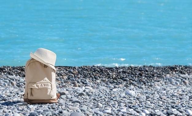 Zomer reizen achtergrond met rugzak en hoed aan de kust