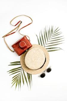 Zomer reizen achtergrond. stro, retro camera, zonnebril en tropisch palmblad. platliggend, bovenaanzicht