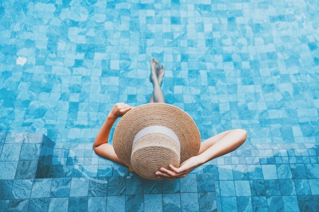 Zomer reizen vakantie concept, gelukkige reiziger aziatische vrouw met hoed en bikini ontspannen in luxe infinity pool hotel resort op dag in phuket, thailand
