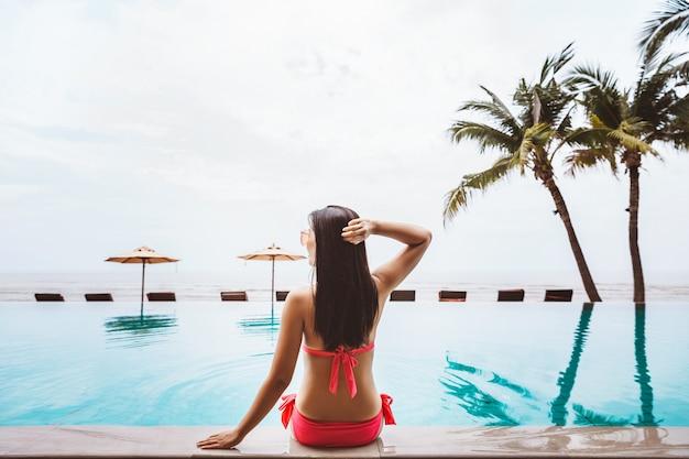 Zomer reizen vakantie concept, reiziger aziatische vrouw met bikini en hoed ontspannen in het overloopzwembad in luxe hotelresort met zee strand in thailand
