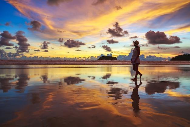 Zomer reizen vakantie concept, reiziger aziatische vrouw met hoed ontspannen en bezienswaardigheden op kata strand bij zonsondergang in phuket, thailand