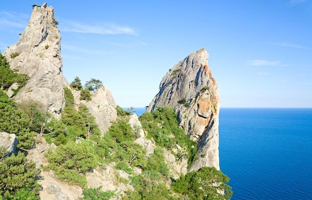 Zomer rotsen op lucht en zee oppervlakte achtergrond (