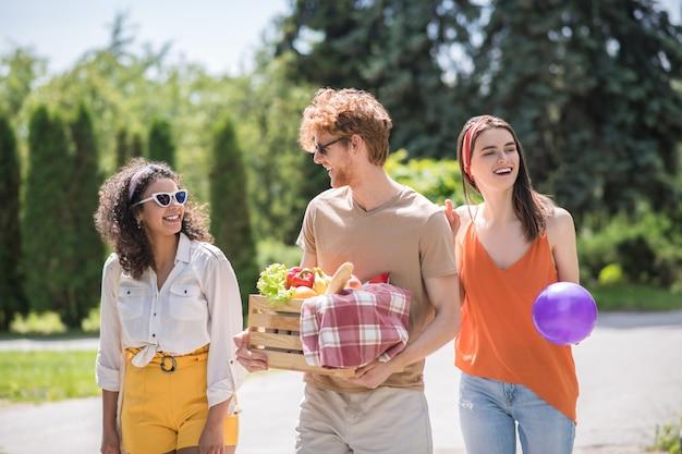 Zomer rust. drie gelukkige lachende jonge mensen in lichte kleding en zonnebrillen wandelen op zomerpicknick in de natuur