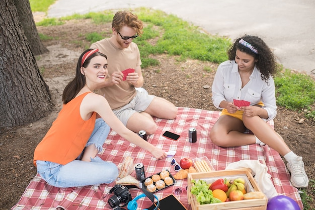 Zomer rust. groep jonge blije mensen met eten, drinken en spelletjes die vrije tijd doorbrengen op picknick in groen park