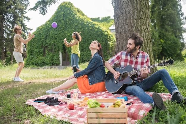 Zomer, rust. jonge, bebaarde man die gitaar speelt voor meisje zittend op deken onder boom en vrienden die bal spelen in glade