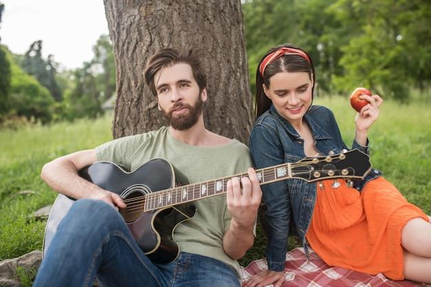 Zomer, rust. jonge, bebaarde man gitaarspelen voor meisje met appel zittend op deken onder boom buitenshuis op fijne middag