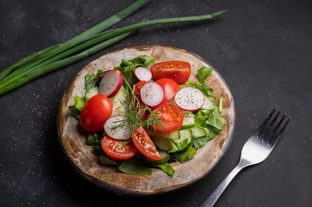 Zomer salade van spinazie, tomaten, radijs, dille op een zwarte achtergrond