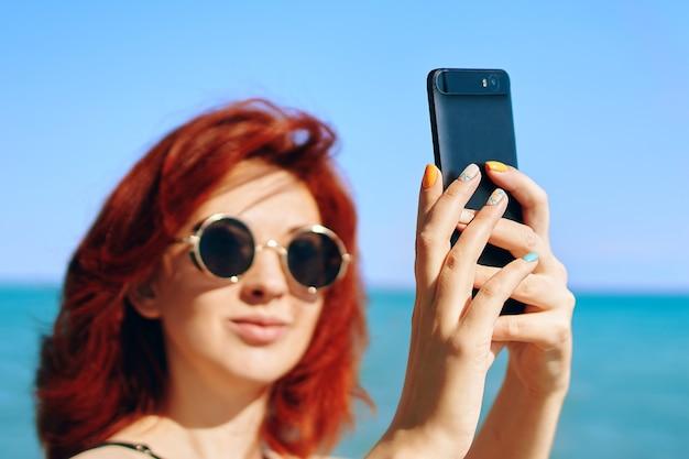 Zomer selfie. mooie vrouw maakt foto's van zichzelf tegen de blauwe zee en de lucht. roodharige vrouw in donkere zonnebril neemt selfie op de camera van de smartphone.