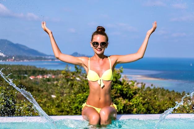 Zomer shoot van gelukkige opgewonden vrolijke jonge vrouw die plezier heeft en water door haar handen laat spetteren bij het overloopzwembad van de villa, luxe leven, reizen op het exotische eiland.