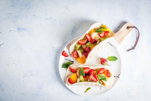 Zomer snacks. eten voor een feestje. fruittaco's met aardbeien, mango's, bananen, chocolade, munt. op een lichtblauwe betonnen tafel. copyspace bovenaanzicht