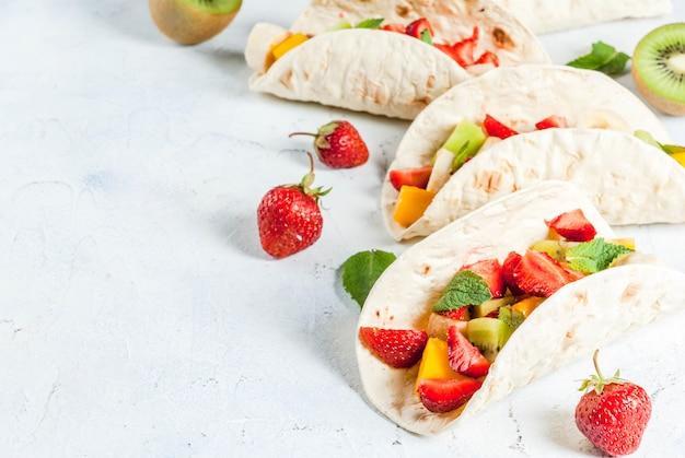 Zomer snacks. eten voor een feestje. fruittaco's met aardbeien, mango's, bananen, chocolade, munt. op een lichtblauwe betonnen tafel. copyspace