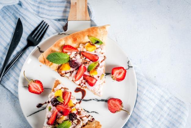 Zomer snacks. eten voor feest. fruitpizza met room, krenten, yoghurt, aardbeien, mango, perziken, bananen, bramen, chocolade, walnoten, munt. op lichtblauwe tafel. bovenaanzicht