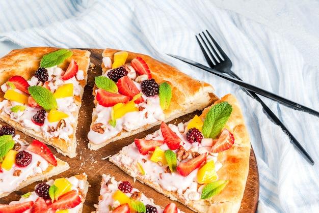 Zomer snacks. eten voor feest. fruitpizza met room, krenten, yoghurt, aardbeien, mango, perziken, bananen, bramen, chocolade, walnoten, munt. op lichtblauwe tafel. copyspace