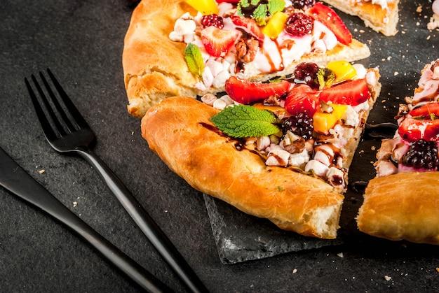 Zomer snacks. eten voor feest. fruitpizza met room, krenten, yoghurt, aardbeien, mango, perziken, bananen, bramen, chocolade, walnoten, munt. op zwarte tafel. copyspace