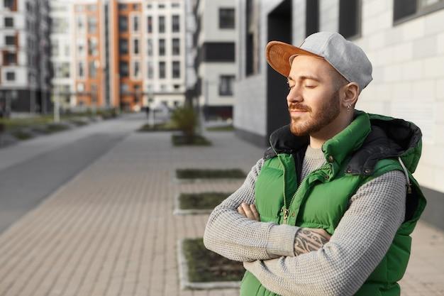 Zomer, stad, mensen en levensstijlconcept. foto van vrolijke modieuze jonge europese man met stoppels armen gekruist op zijn borst, ogen sluiten, genieten van warme glans van de ochtendzon