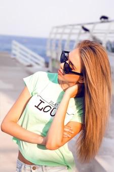 Zomer stadsportret van stijlvolle tiener girt, alleen reizen met rugzak, mooie dag hebben in de nieuwe stad, genieten van haar vakantie, rugzak, hipster bril en casual look dragen