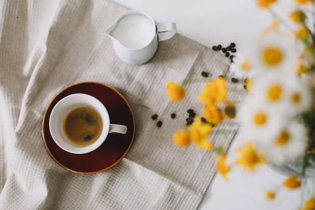 Zomer stilleven scène met wilde bloemen, kopje koffie en melkkan op witte tafel