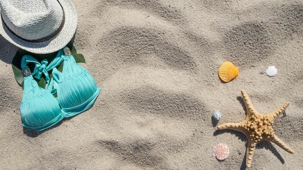 Zomer strand achtergrond. hoed, badpak, zeester en schelpen. bovenaanzicht
