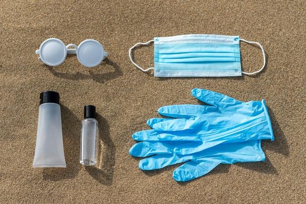 Zomer strand lay-out met zonnebril, beschermende handschoenen, medisch masker en handdesinfecterend middel op zand