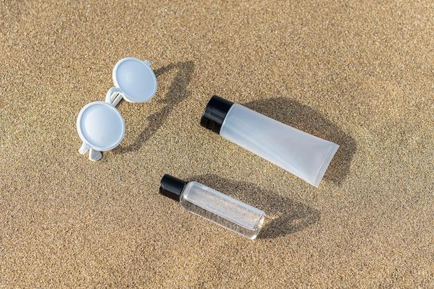 Zomer strand lay-out met zonnebril en handdesinfecterend middel op zand