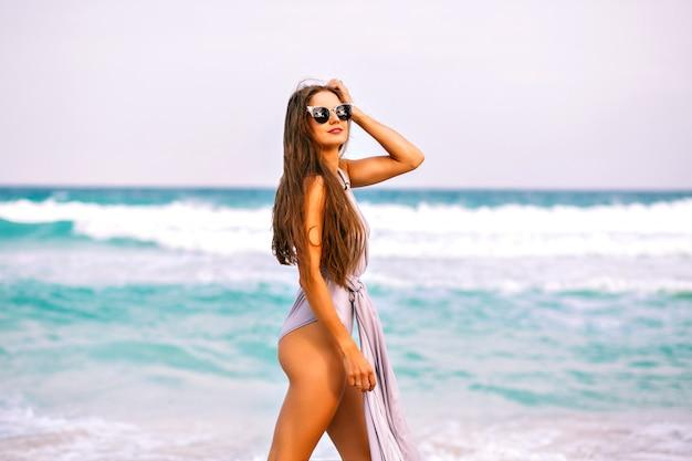 Zomer strand portret van mooie brunette vrouw met sportieve perfect gebruinde lichaam en lange donkerbruine haren, trendy glamour elegante zwembroek dragen, model ontspannen in de buurt van de oceaan, draaien en plezier hebben, vrijheid.
