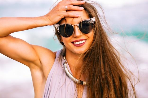 Zomer strand portret van mooie brunette vrouw met sportieve perfect gebruinde lichaam en lange donkerbruine haren, trendy glamour elegante zwembroek dragen, model ontspannen in de buurt van oceaan, zonnebril en sieraden.