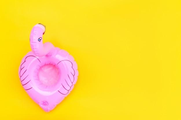 Zomer strand samenstelling. eenvoudig minimaal ontwerp met roze opblaasbare flamingo geïsoleerd op gele achtergrond. pool float party, trendy celebrity fashion concept. plat lag bovenaanzicht kopie ruimte.