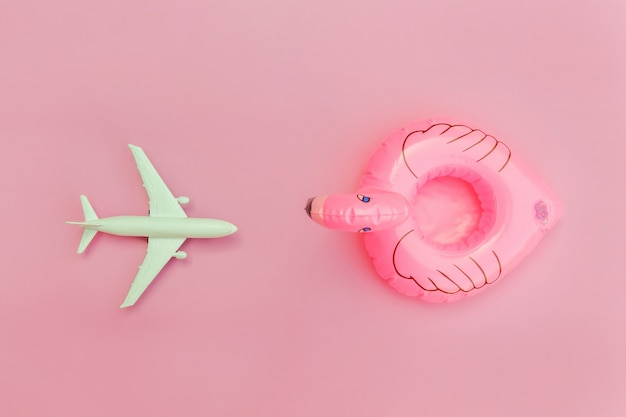 Zomer strand samenstelling. minimale eenvoudige plat lag met vliegtuig en opblaasbare flamingo geïsoleerd op pastel roze achtergrond. vakantie reizen avontuurlijke reis concept. bovenaanzicht kopie ruimte.