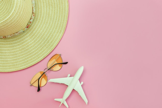Zomer strand samenstelling. minimale eenvoudige plat lag met vliegtuig zonnebril en hoed geïsoleerd op pastelroze. vakantie reizen avontuurlijke reis concept. bovenaanzicht kopie ruimte.