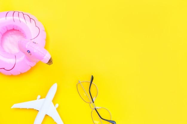 Zomer strand samenstelling. minimale eenvoudige plat lag met vliegtuig zonnebril en opblaasbare flamingo geïsoleerd op gele achtergrond. vakantie reizen avontuurlijke reis concept. bovenaanzicht kopie ruimte.