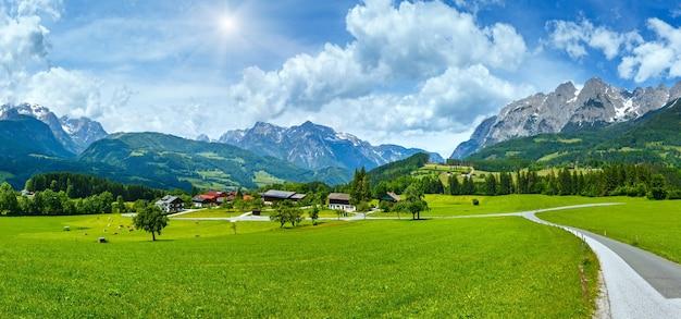 Zomer sunshiny alpine bergland panorama met grazige weide en weg naar dorp (oostenrijk)