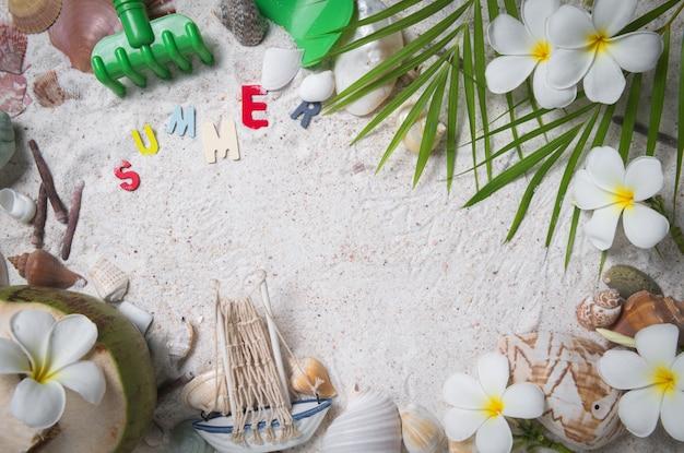 Zomer tekst met schelpen en plumeria bloemen op zand